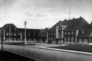 Plac Dworcowy przed 1930 rokiem, tuż po oddaniu. Drzewa dopiero posadzone, brakuje krzewów po środku placu. Ulica i chodnik jeszcze nie wybrukowane, nie ma jeszcze płotka drewnianego pomiędzy ulicą a prawą częścią obiektu.