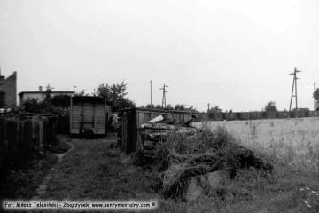 Lwówek w lipcu 1985 roku. Po przeciwnej stronie ulicy koło dworca kolejki widok fragmentu linii wąskotorowej do Komorowa nie czynnej od 1963 roku.