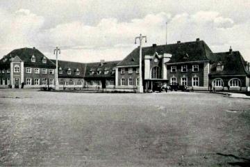 Plac Dworcowy w latach 20 tych, Roślinność jeszcze niska, komin w prawym skrzydle jeszcze niski, ulice i chodnik wybrukowane.