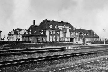 Widok dworca osobowego z 1930 roku od strony torów. Przejście naziemne zastąpiono tunelami dopiero za 14 lat. Po lewej stronie widać wybudowany w 1929 roku budynek symetryczny do poczty, nie połączony jeszcze niską częścią z resztą obiektu. W oddali na przeciwko dworca widać reklamę Banku Międzyrzeckiego.