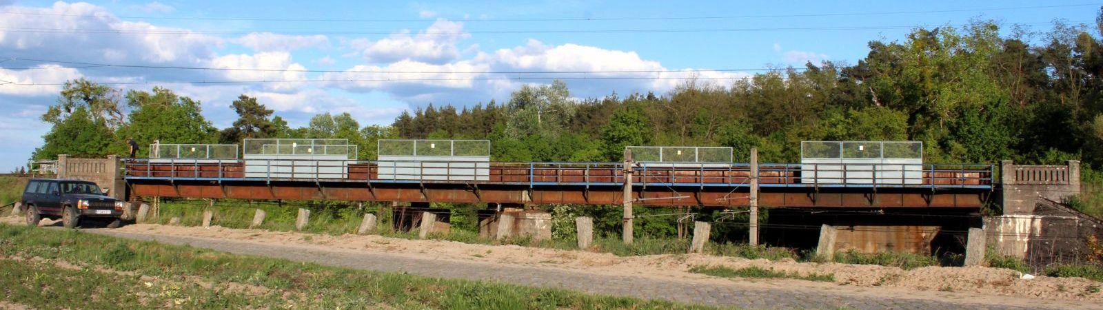 Wiadukt w kierunku Babimostu - Podmokli, gdzsie kończył się nowo wybudowany odcinek toru. Szlak Zbąszynek - Podmokla był zawsze jednotorowym, natomiast drugi tor rozpoczynał się w miejscu, gdzie nowy pojedynczy stykał się ze starym oddanym w dniu 26.06.1870 roku. Krótki odcinek pojedynczego toru, miał długość 7.6 km. Rozwidlał się w podmoklach na 88.3 kilometrze starej linii. Uruchomiono go 24.11.1925 roku, dla ruchu towarowego, a do 1930 roku, przystanek osobowy tymczasowy znajdował się w budowanym Zbąszynku tuż nad szosą prowadzącą z Kosieczyna do Zbąszynka. Wiadukt, który widzimy na powyższym zdjęciu był zawsze jednotorowym, mimo że śmiałe plany zakłądały ruch po dwóch niezależnych.